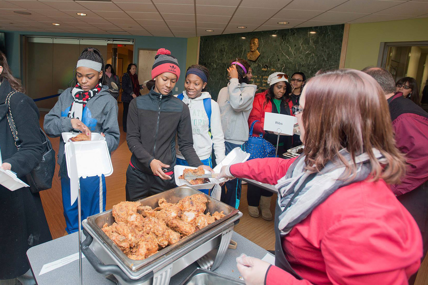 Attendees go through the food line at one of KCC's annual Soul Food Luncheon events.