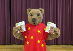 "KCC mascot Blaze holds copies of the College's new children's book ""Blaze Goes to College."""