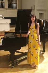 KCC alumnu Abigail Mullis stands next to a piano.
