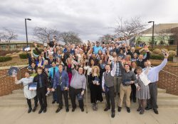 A group photo of KCC's 2019 Outstanding Bruin Award winners and presenters celebrating on the steps at the front of KCC's North Avenue campus in Battle Creek.