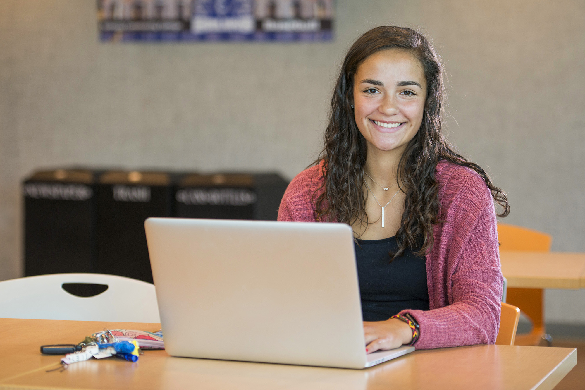 A student poses with a laptop in the Student Center.