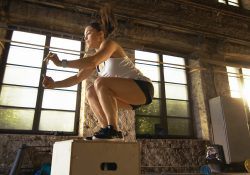 A woman jumps on a box while doing plyometric exercises.