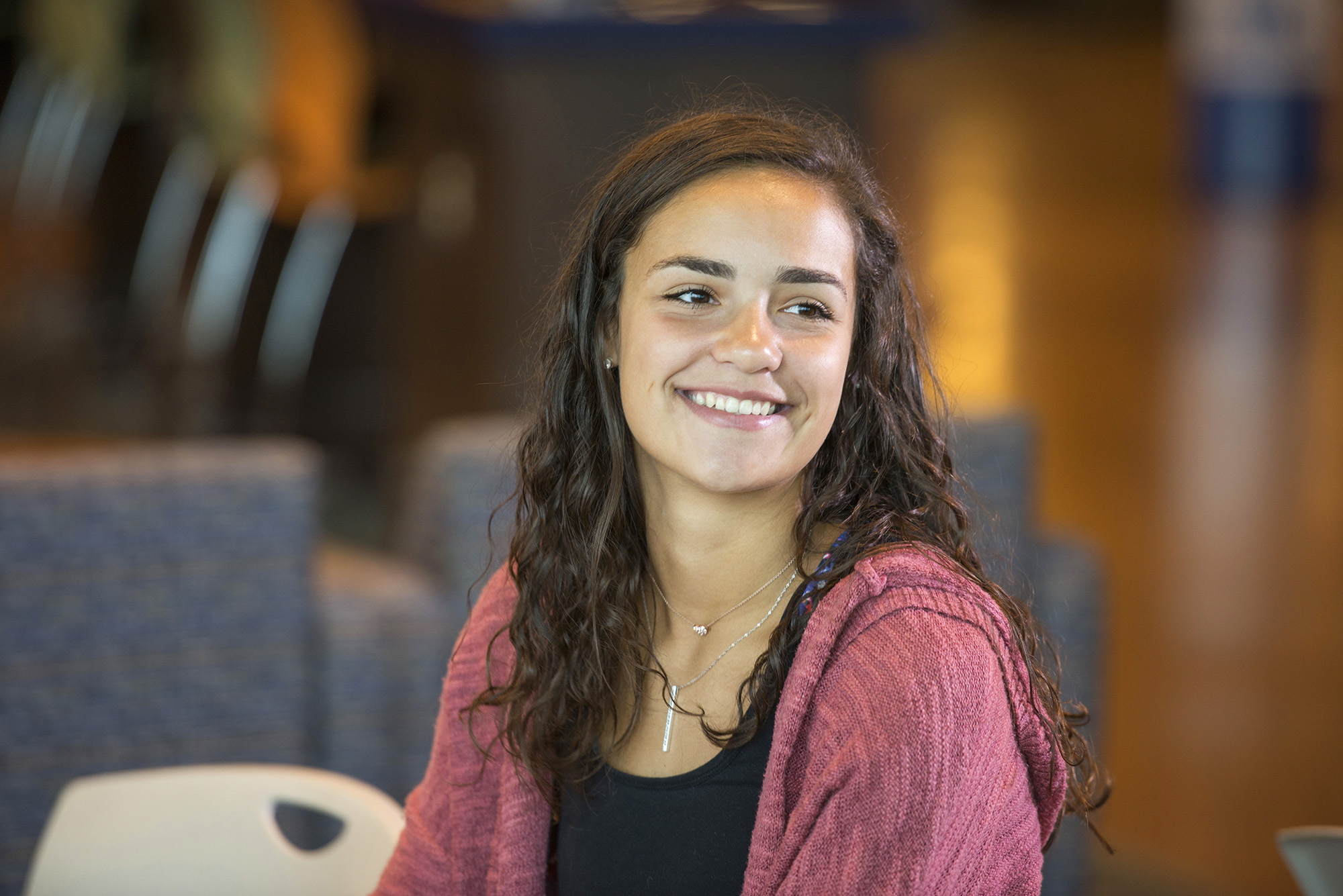 A female student smiles in the Student Center.