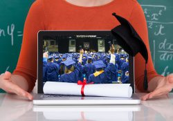 Closeup of a laptop screen showing an image of college graduates, along with a diploma and commencement cap.