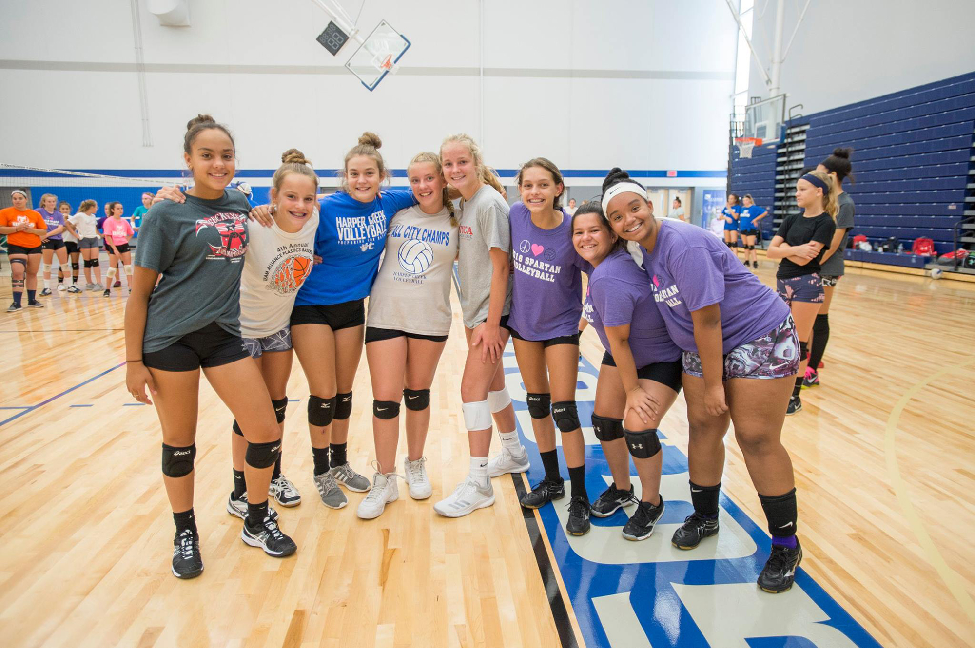 Youth volleyball camp participants pose for a group photo in the Miller Gym.
