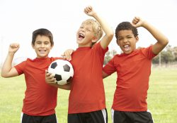 Three boys pose with a soccer ball.