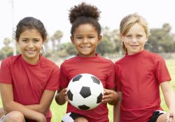 Three girls pose with a soccer ball.