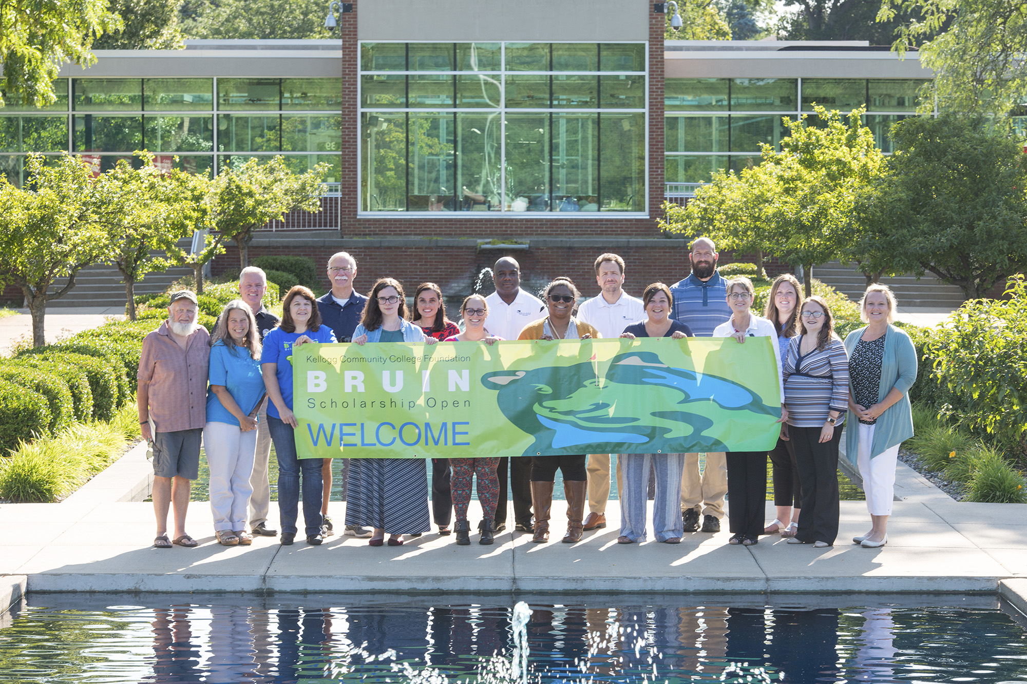 A group photo of KCC staff and Bruin Open volunteers holding a Bruin Scholarship Open banner between the reflecting pools on campus.