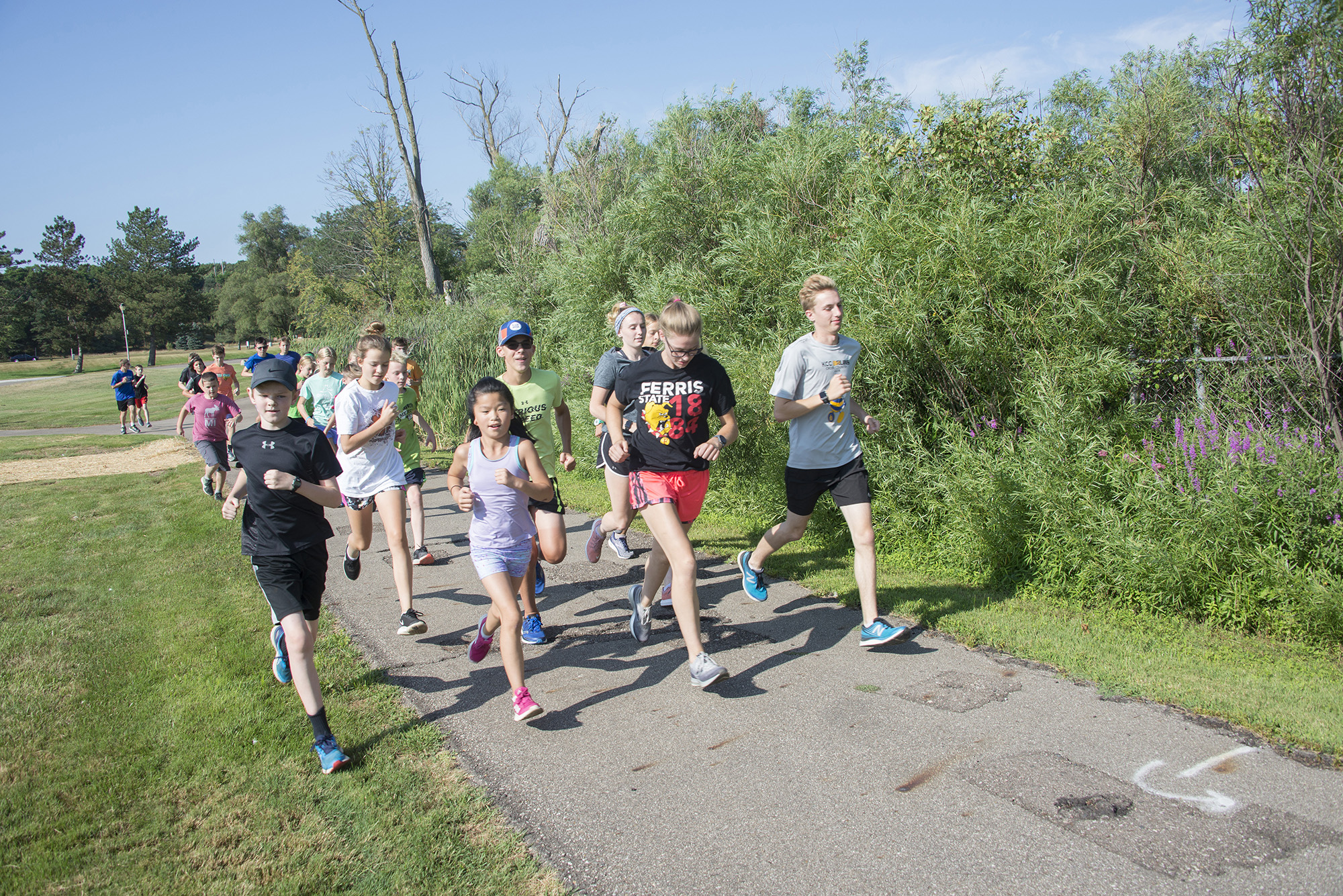 KCC cross country runners run with youth campers around Spring Lake.