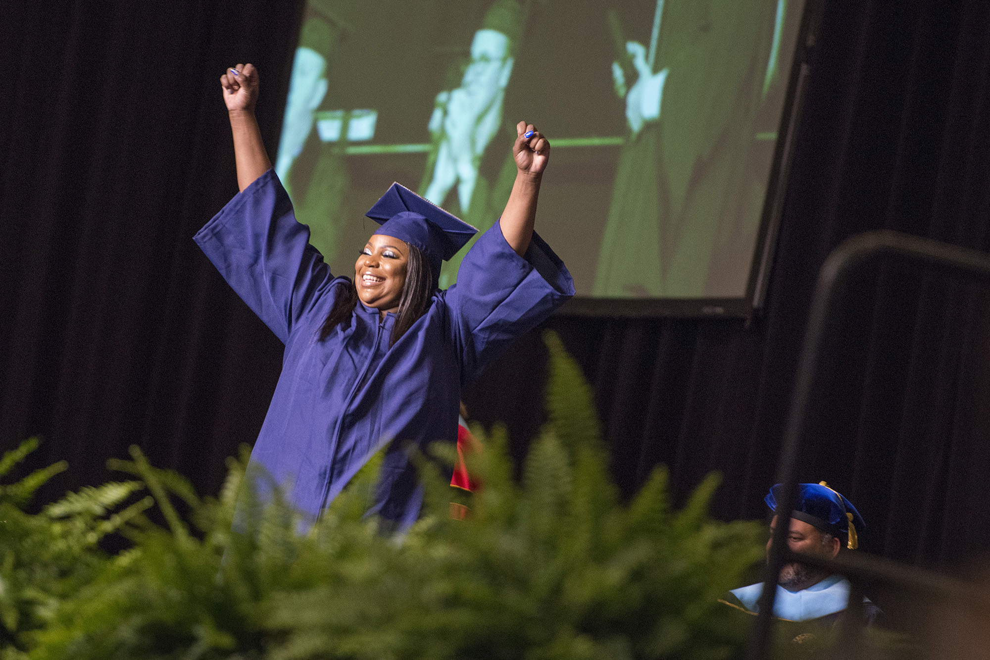 A graduate celebrates onstage during KCC's 2019 commencement ceremony.
