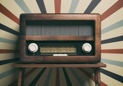 An old radio in front of colorful wallpaper.