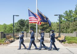 A military color guard carries the U.S. and Michigan flags during a Memorial Day event on campus.