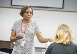 KCC alum and adjunct instructor Nikeesha Settles hands out papers during a class.