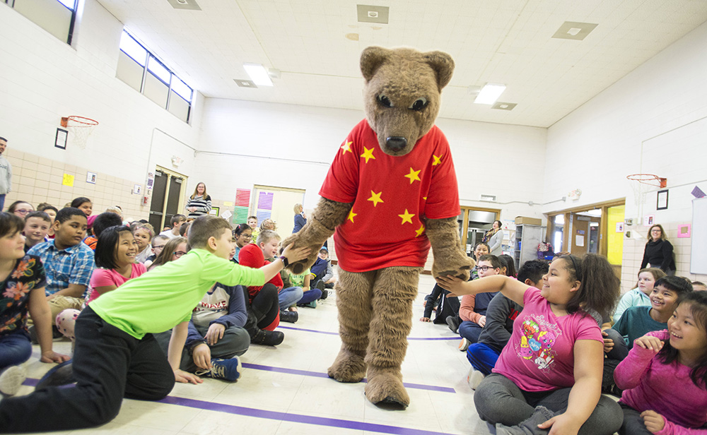 KCC mascot Blaze gives kids high-fives during a reading event at a local elementary school.