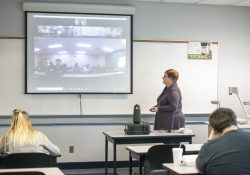 History professor Michelle Wright teaches a class on campus in Battle Creek while teaching students in Albion remotely via a video feed.