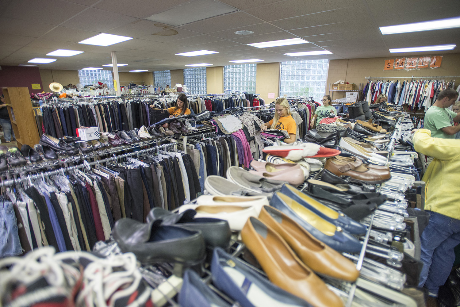 Bruins Give Back participants organize clothes on racks at the Charitable Union.