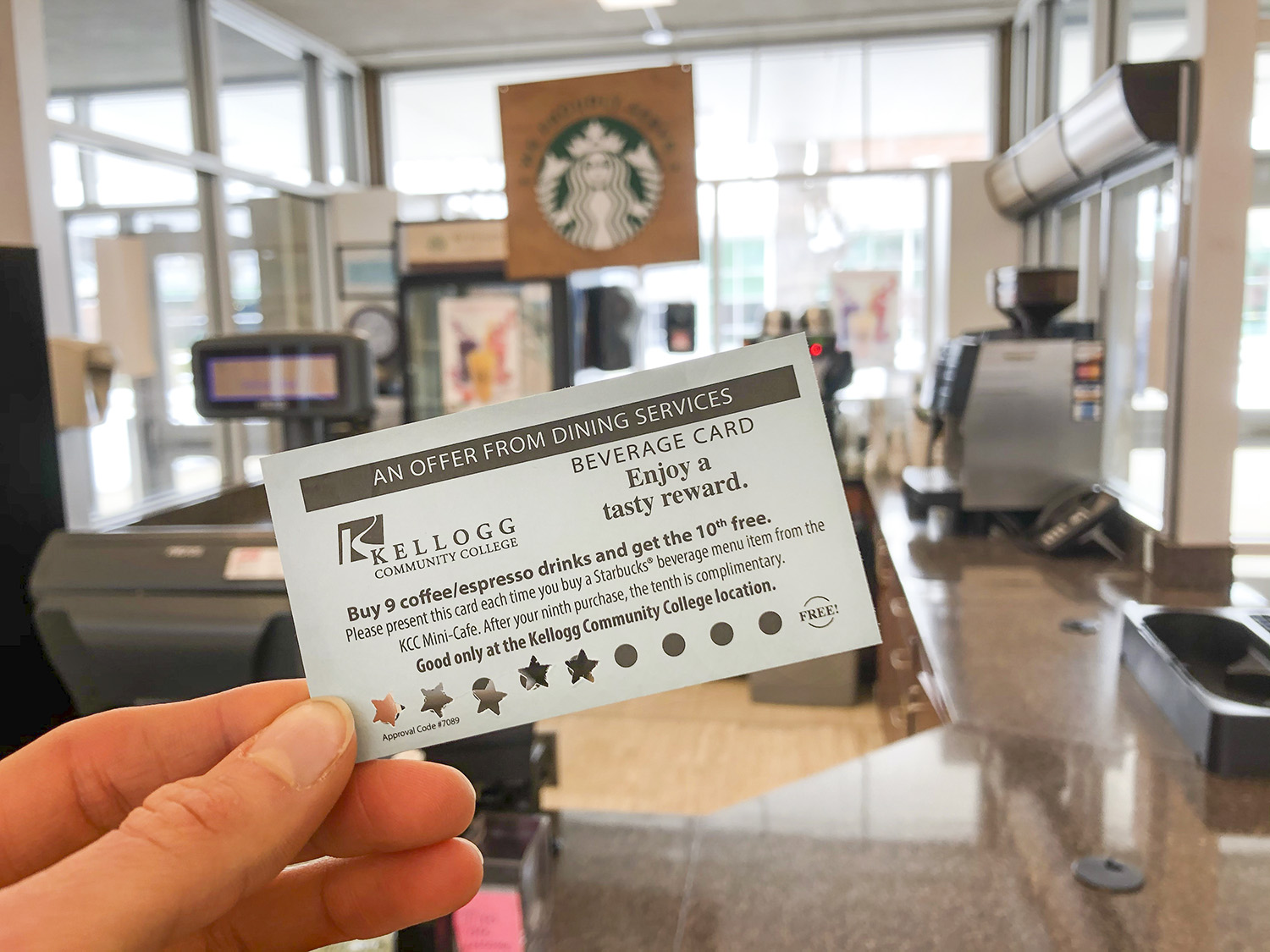 A hand holds a free-coffee card in the foreground with KCC's Mini Cafe in the background.