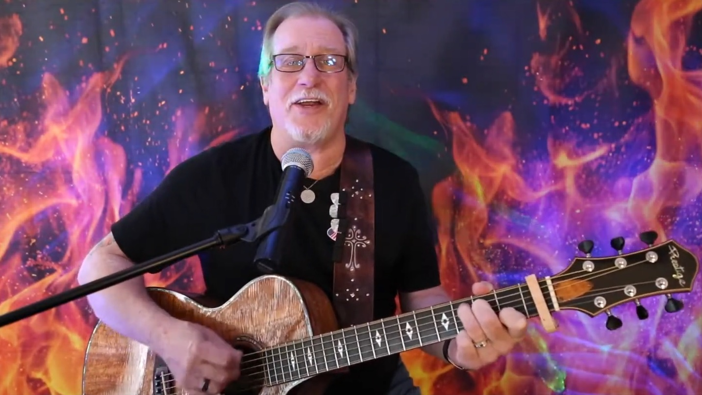 Guitar instructor Paul Freeburn plays guitar and sings into a microphone.