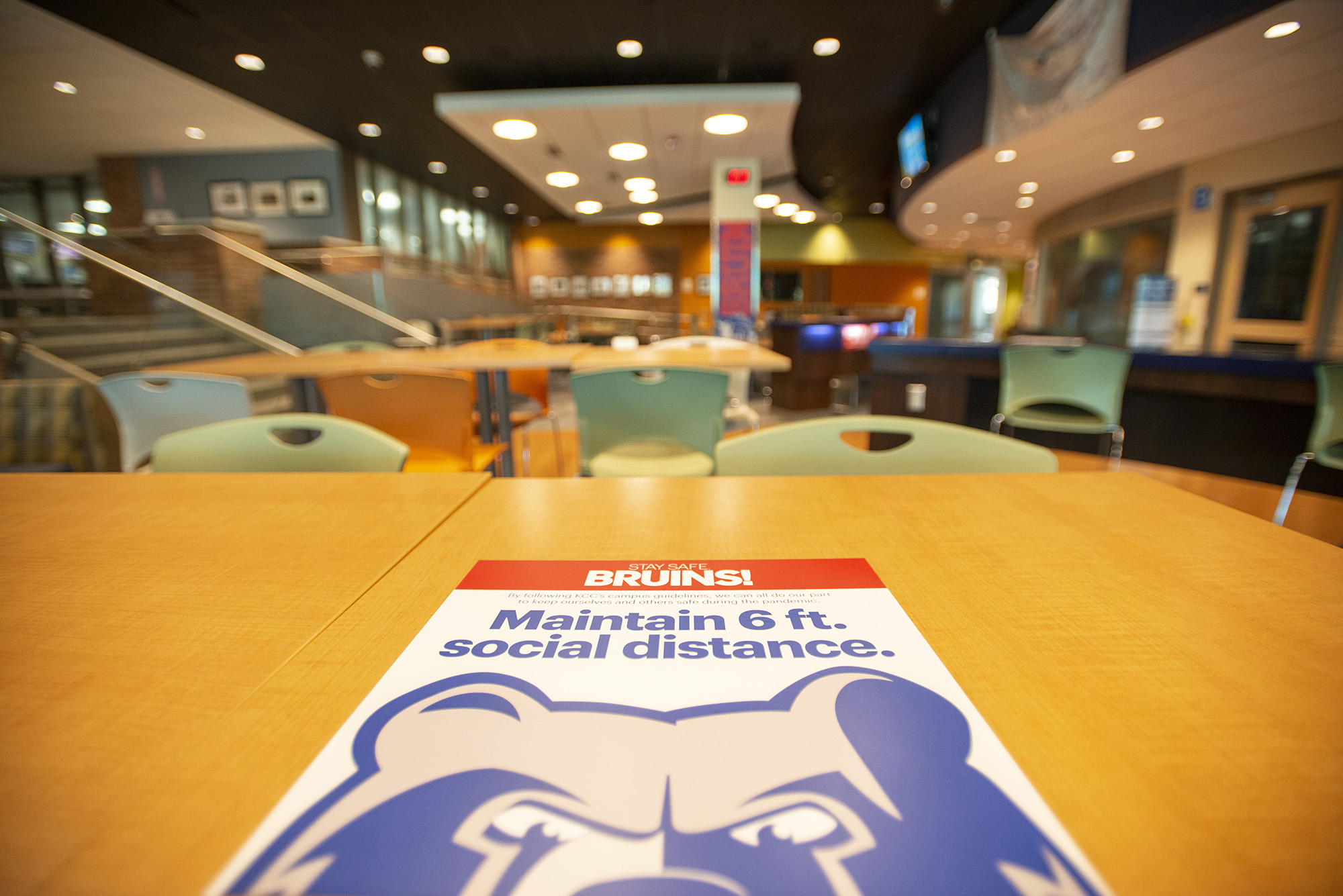A sign encouraging visitors to campus to social distance at least 6 feet apart, affixed to a table in the Student Center.