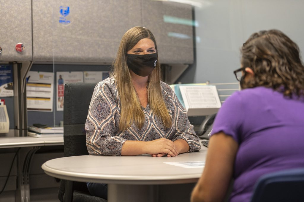 A KCC employee speaks with another employee from behind a protective barrier while wearing a face mask.