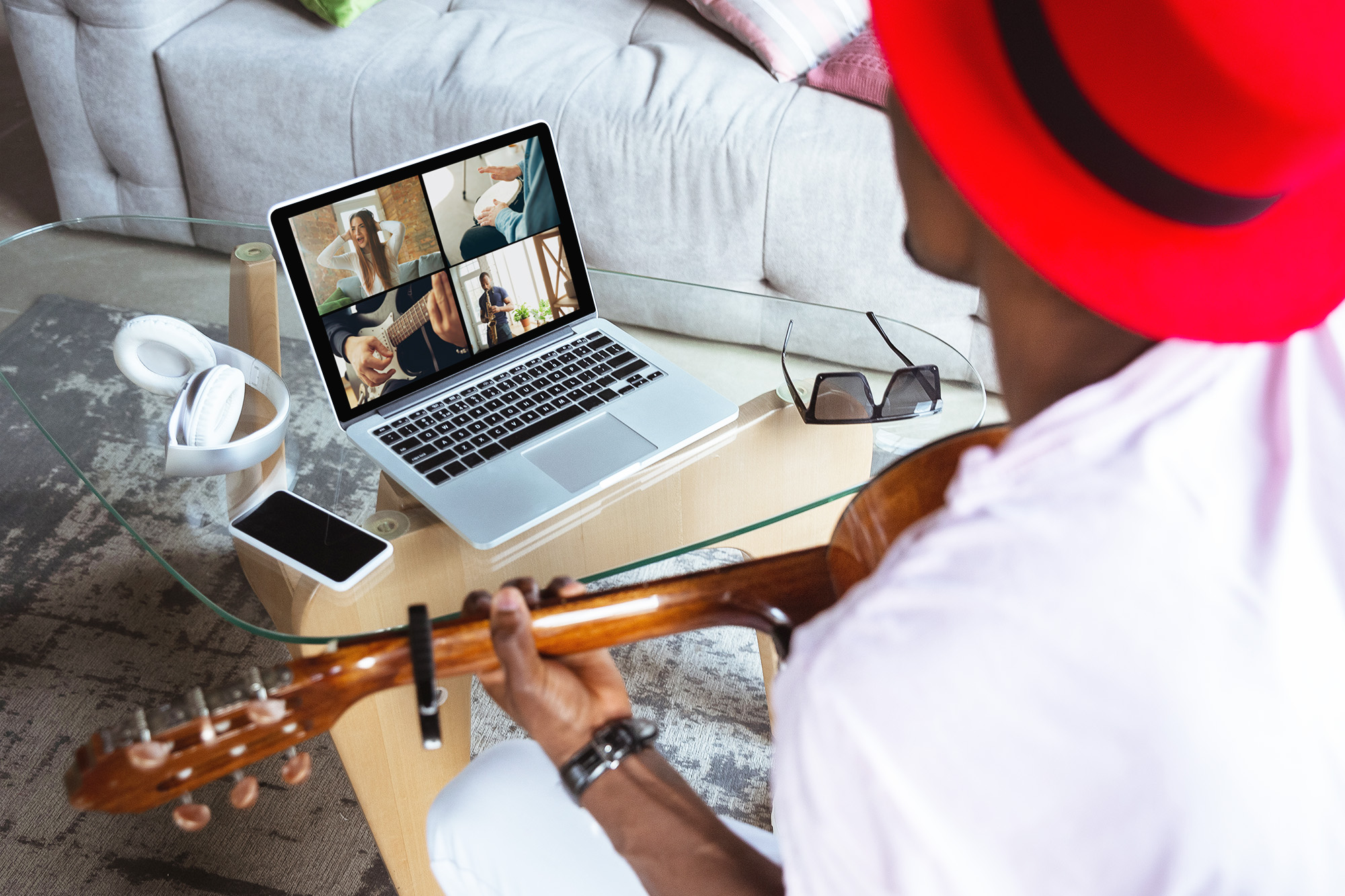A man playing guitar watches a laptop screen where four other people are singing and/or playing instruments.