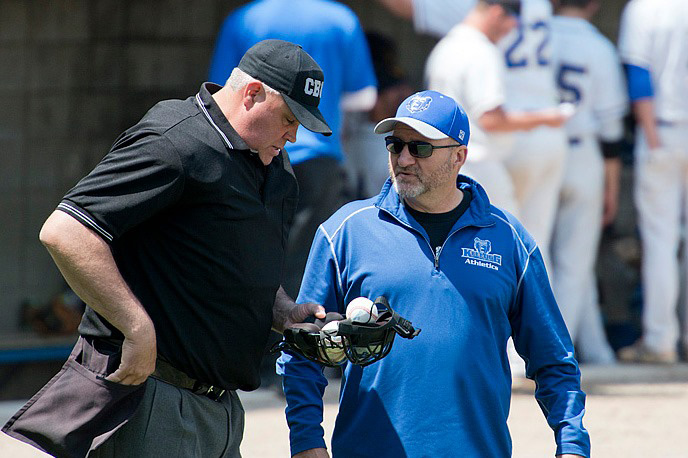 KCC Athletic Director Tom Shaw speaks with an umpire during a baseball game.