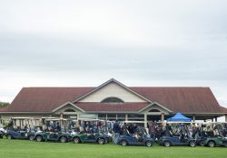 Golf carts and golfers lined up in front of the clubhouse at Binder Park Golf Course.