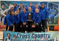The KCC cross country teams pose with a trophy at the National Championship meet.
