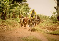 A man rides a bike while being chased by smiling kids.