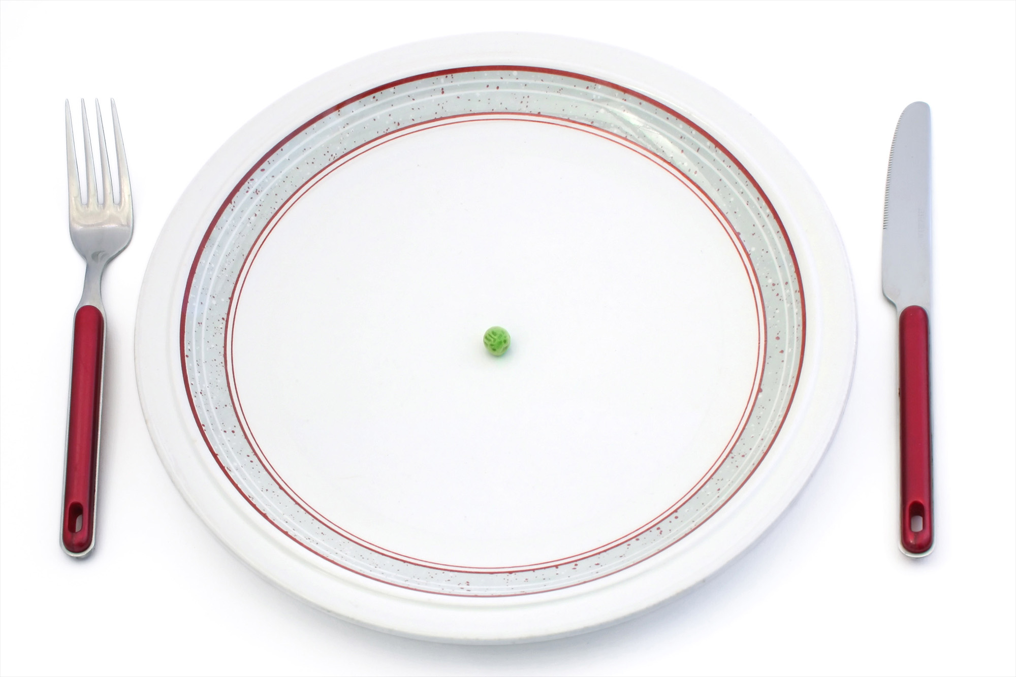A fork and knife by a plate empty except for a single pea.