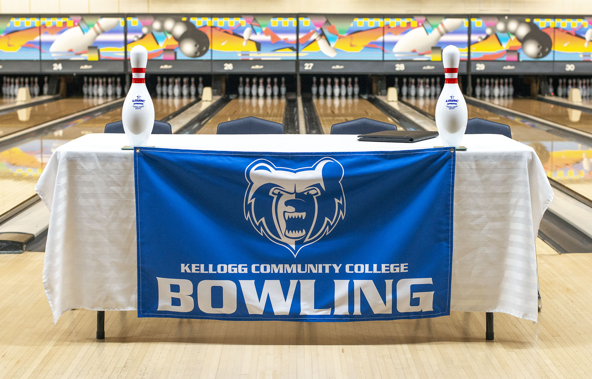 "A table in a bowling alley covered with a cloth featuring the KCC logo and the words ""Kellogg Community College Bowling."""