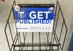 "An empty rack with a sign on it that reads ""Get published! Mosaic."""