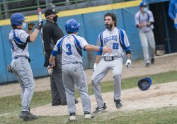 KCC baseball players celebrate after scoring a run.
