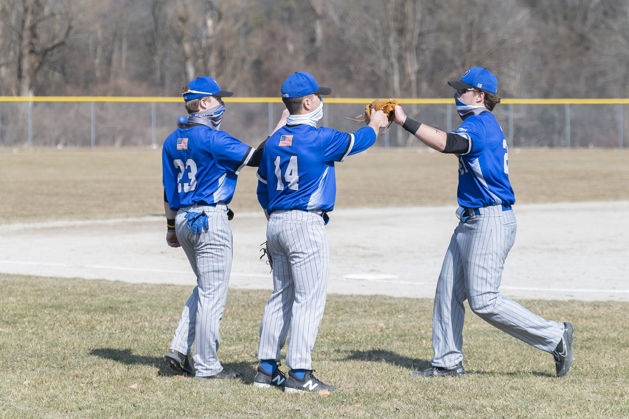 KCC baseball players greet each other off the field between innings.