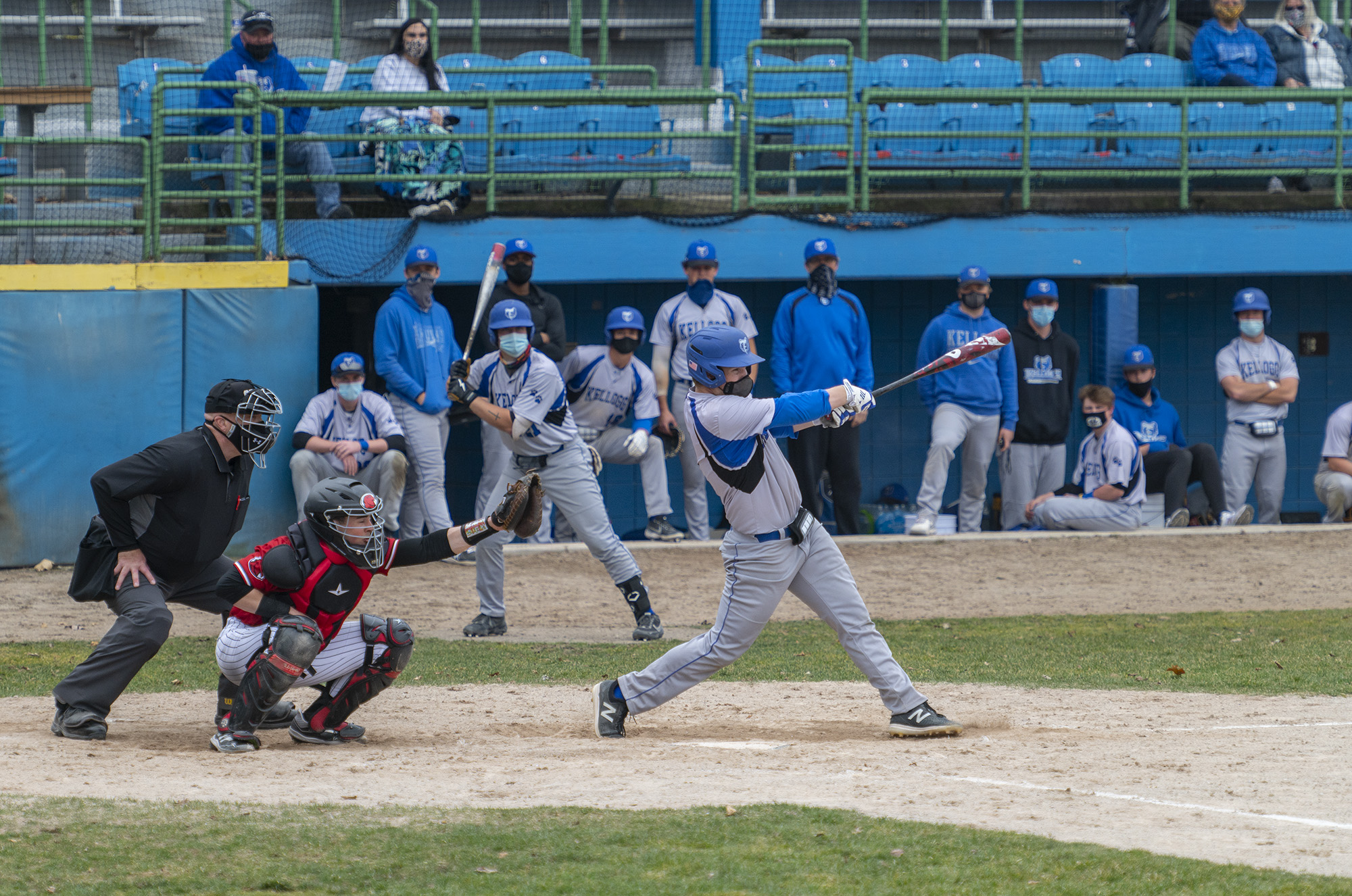 A KCC batter hits the ball as the team watches from the dugout.