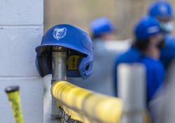 A batting helmet with the KCC Bruin head logo on it sits on a fence during a game.