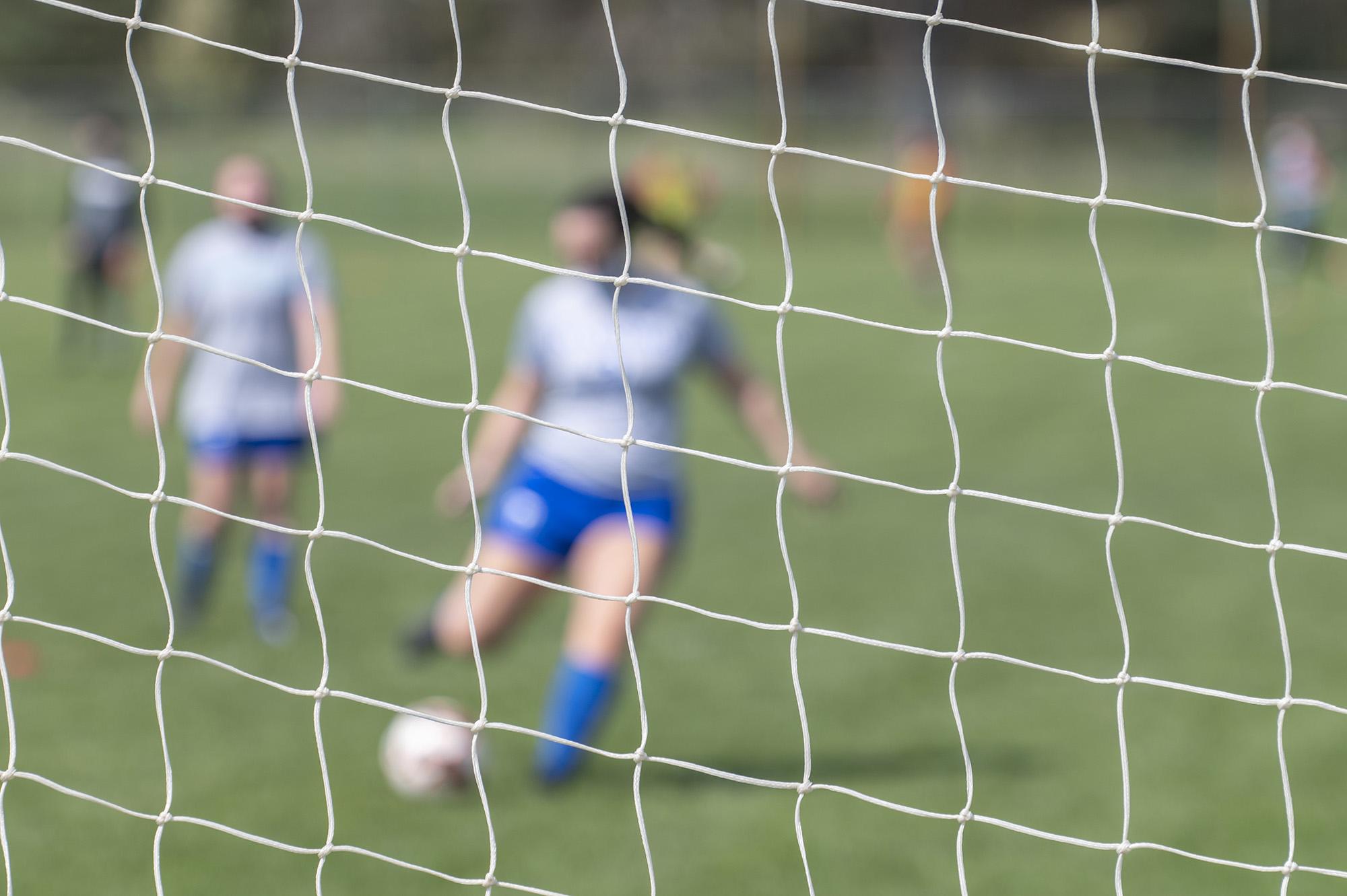 A soccer player kicks a ball into the goal.