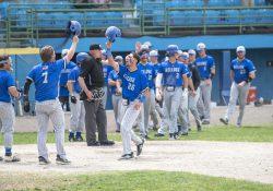 KCC baseball players celebrate after scoring runs.