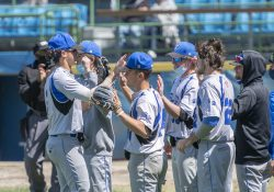 KCC baseball players high-five on the way to the dugout during a game.