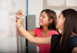 Math students write on a whiteboard.