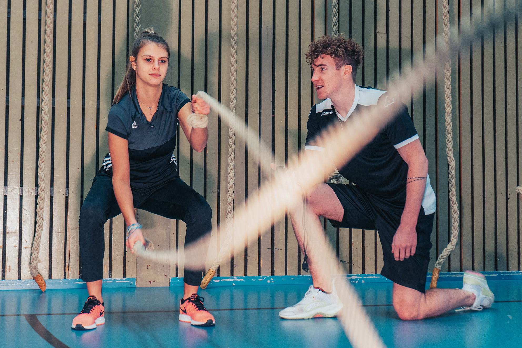 A woman does exercises with ropes while a trainer encourages her from the side.