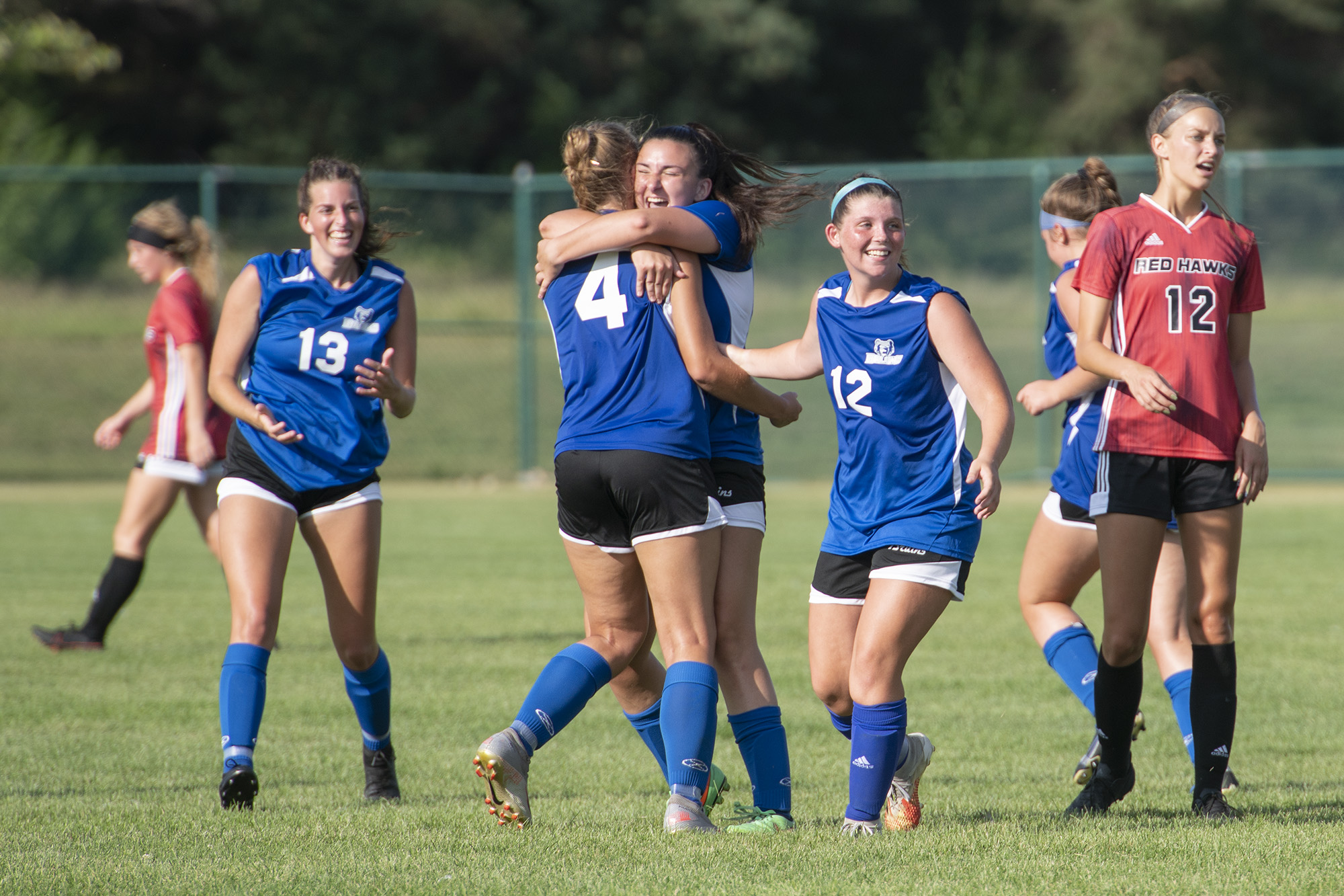 Members of the women's soccer team celebrate after scoring a goal.