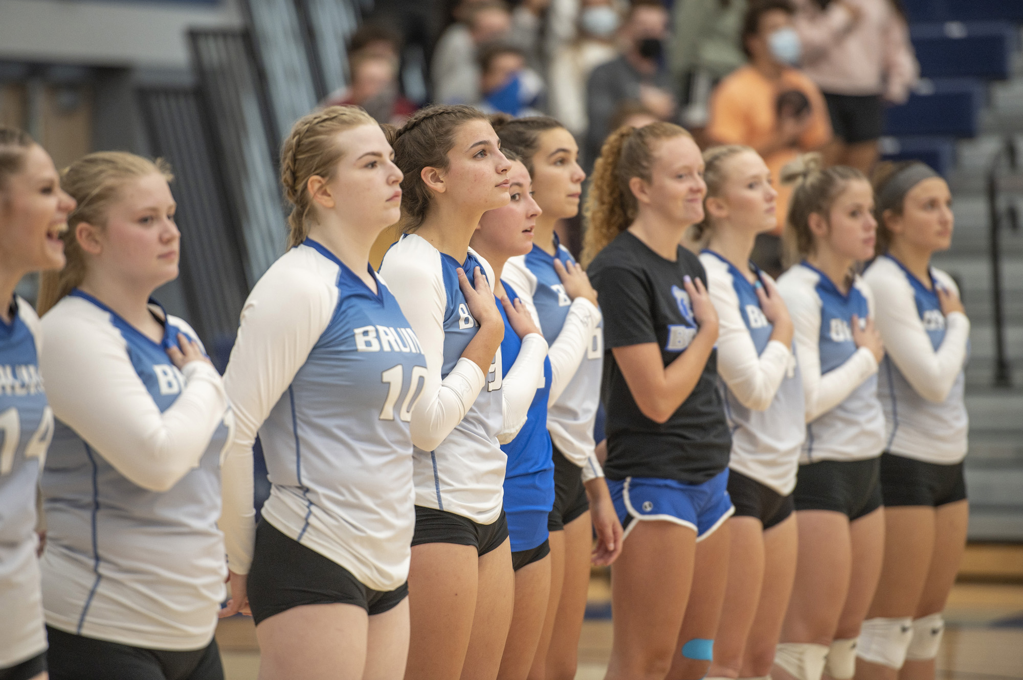 The women's volleyball team stands for the National Anthem before a home match.
