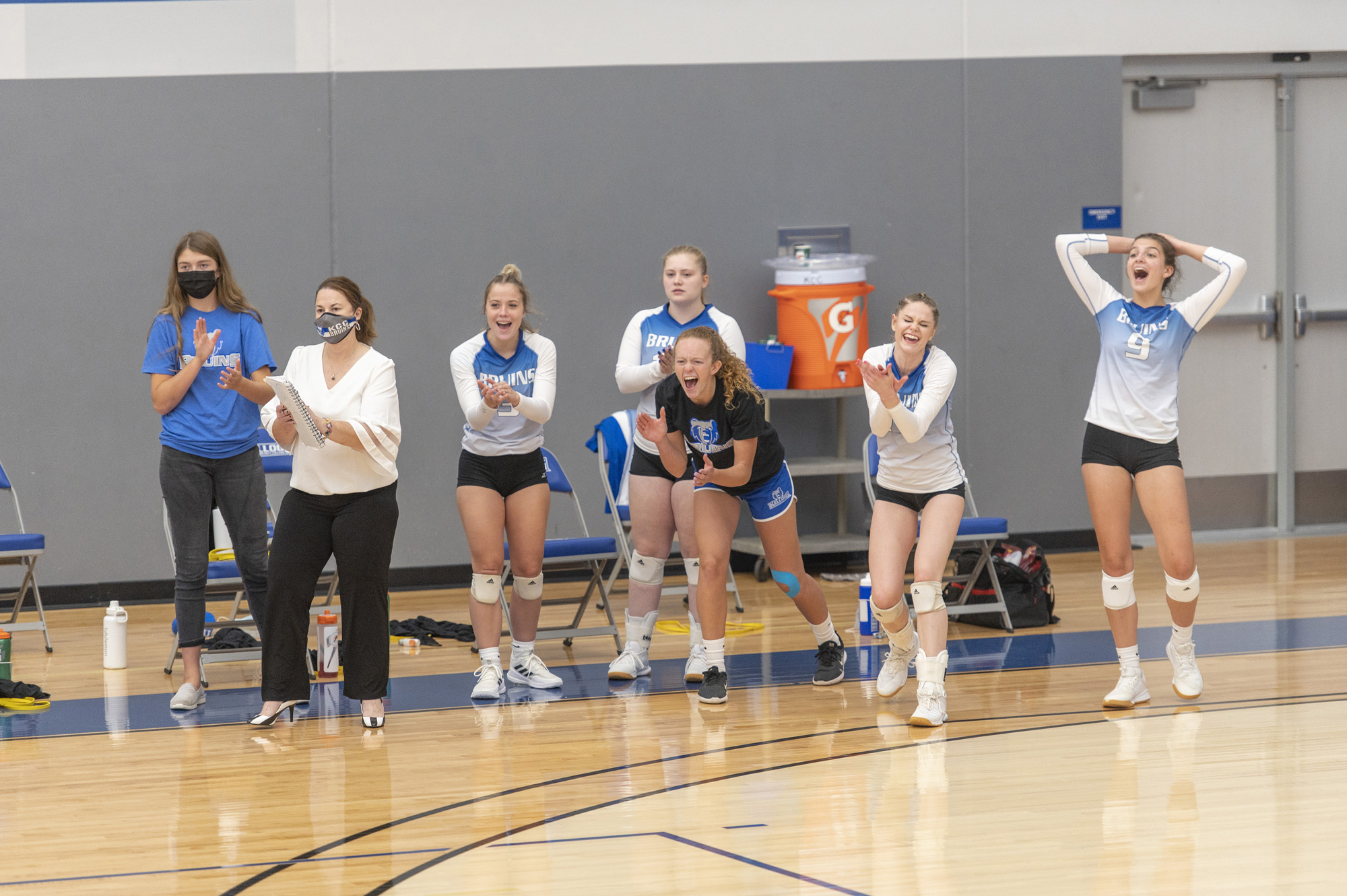 The women's volleyball team celebrates on the sideline after scoring a point.