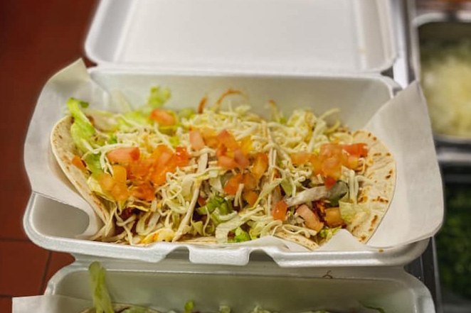 Soft-shell tacos in a to-go container.