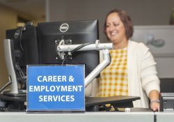 """An employee works on a computer behind a sign that reads """"Career & Employment Services."""""""